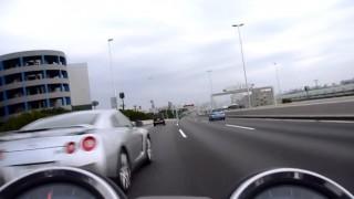 左側から強烈な加速でバイクを追い越していく日産・GTR(R35) 首都高速湾岸線