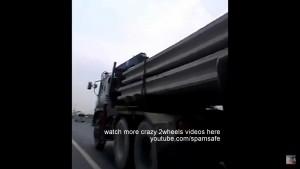 原付に乗った若者が走行中の巨大トレーラーの下をくぐり抜ける危険スタント まさにクレイジー
